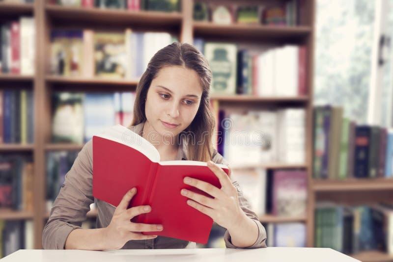 Libro de lectura de la mujer joven imágenes de archivo libres de regalías