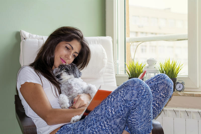 Libro de lectura de la mujer joven con su perro en casa fotografía de archivo