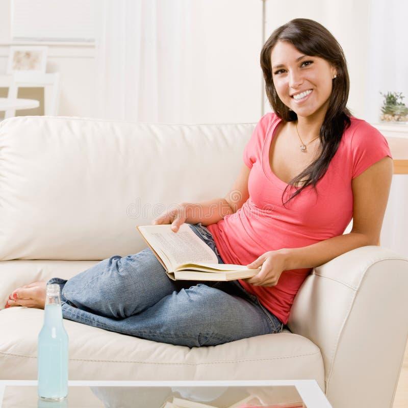 Libro de lectura de la mujer joven en el sofá en el país foto de archivo