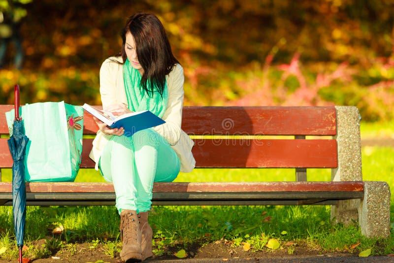 Libro de lectura de la mujer que se sienta en banco en parque imagen de archivo libre de regalías