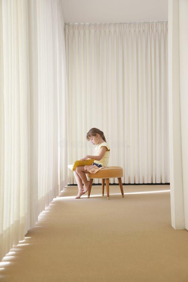 Libro de lectura de la niña en taburete fotografía de archivo libre de regalías
