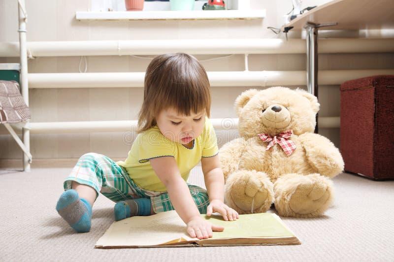 Libro de lectura de la niña interior en su sitio en la alfombra con el oso de peluche del juguete, niño lindo que juega la escuel imagenes de archivo