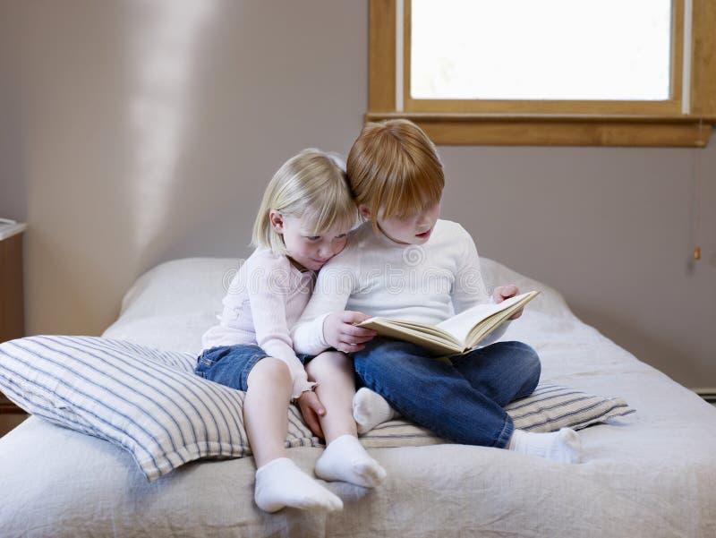 Libro de lectura de las hermanas en cama imagenes de archivo
