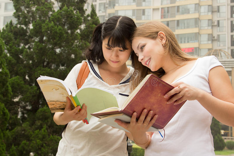 Libro de lectura de las mujeres jovenes en el parque verde imágenes de archivo libres de regalías