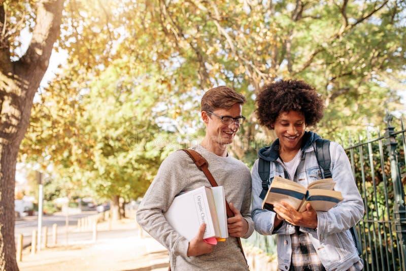 Libro de lectura de los estudiantes universitarios en el campus de la universidad fotografía de archivo libre de regalías