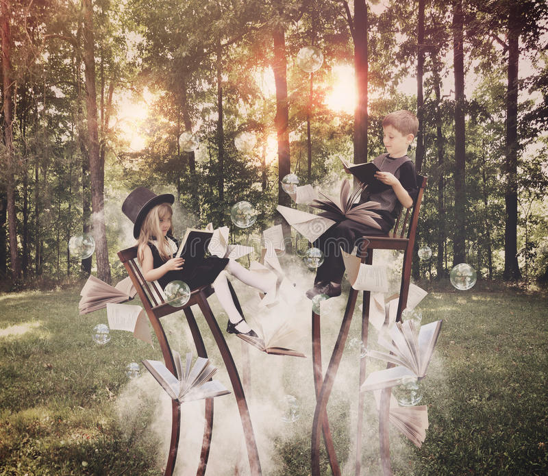 Libro de lectura de los niños en bosque en sillas largas imagen de archivo