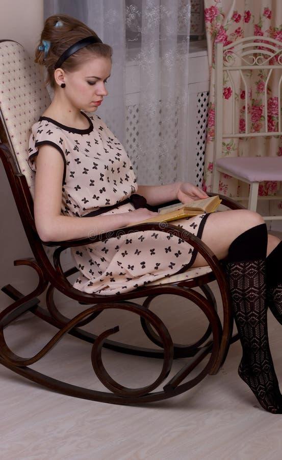 Libro de lectura de relajación de la muchacha en la floración foto de archivo