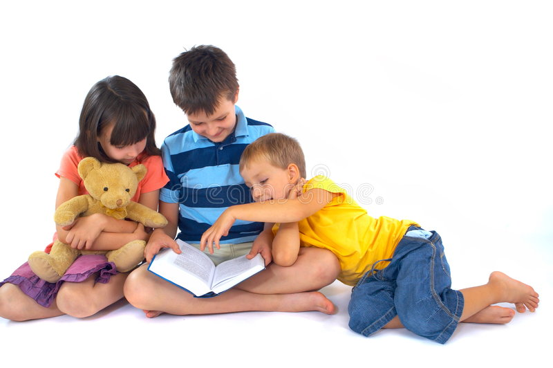 Libro de lectura de tres niños imagen de archivo