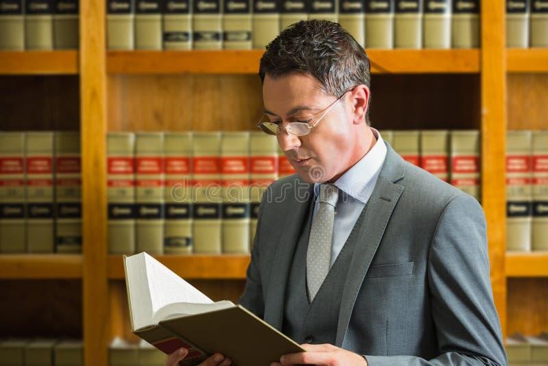 Libro de lectura del abogado en la biblioteca jurídica foto de archivo