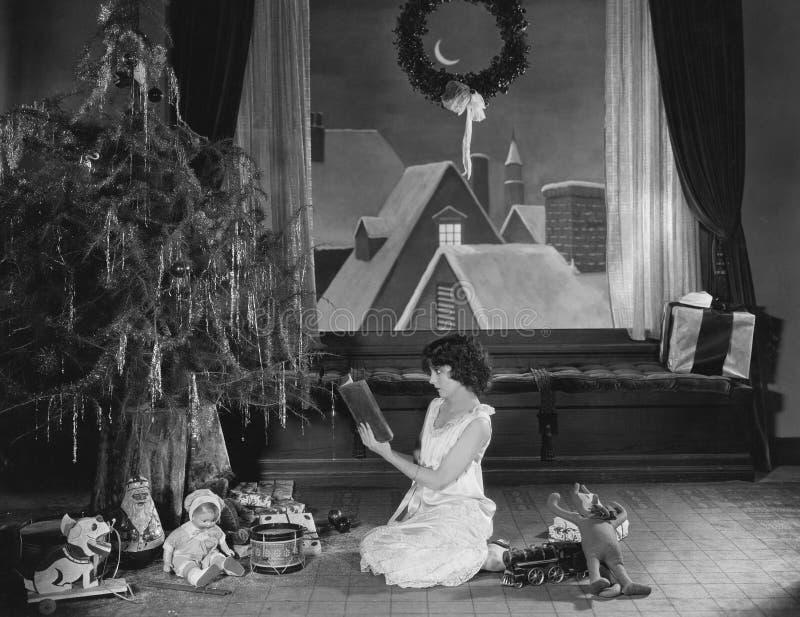 Libro de lectura del adolescente con el árbol de navidad (todas las personas representadas no son vivas más largo y ningún estado foto de archivo libre de regalías