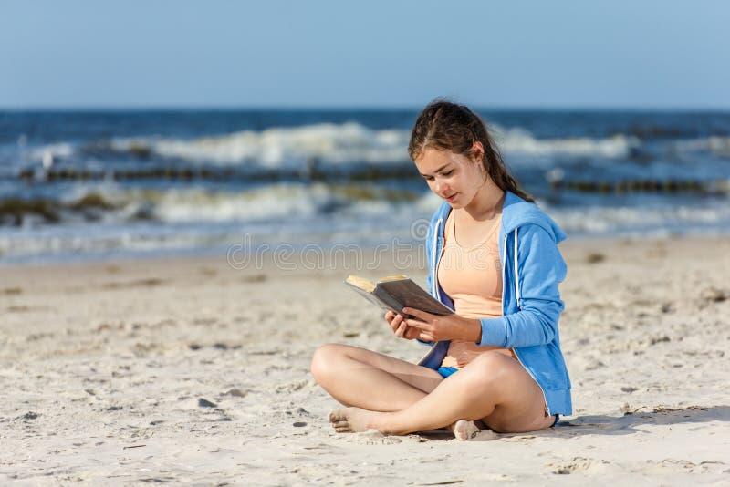 Libro de lectura del adolescente que se sienta en la playa imagenes de archivo