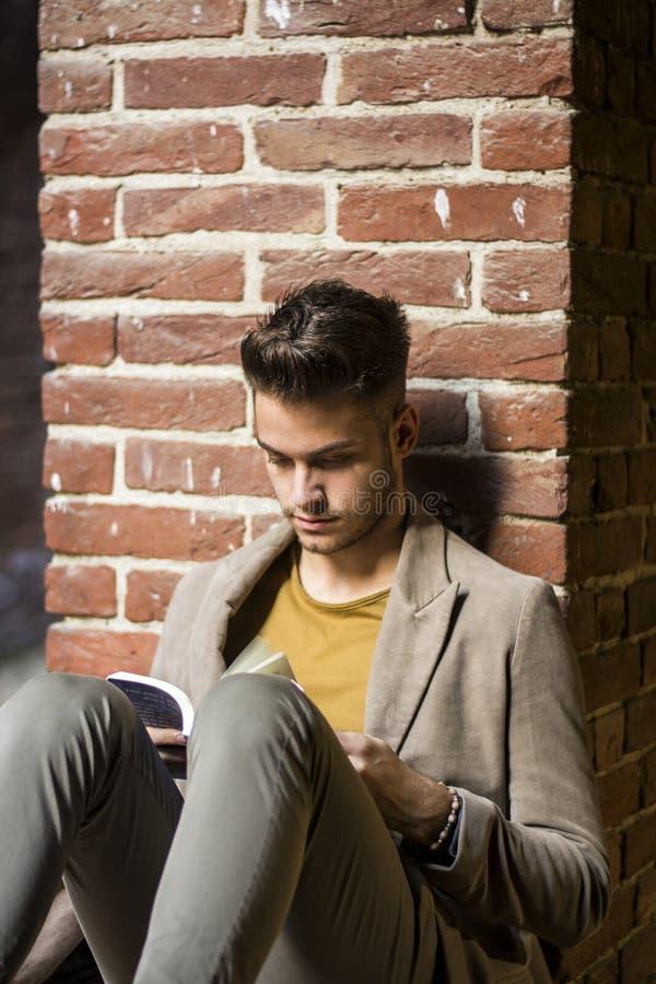 Libro de lectura del estudiante masculino al aire libre imágenes de archivo libres de regalías