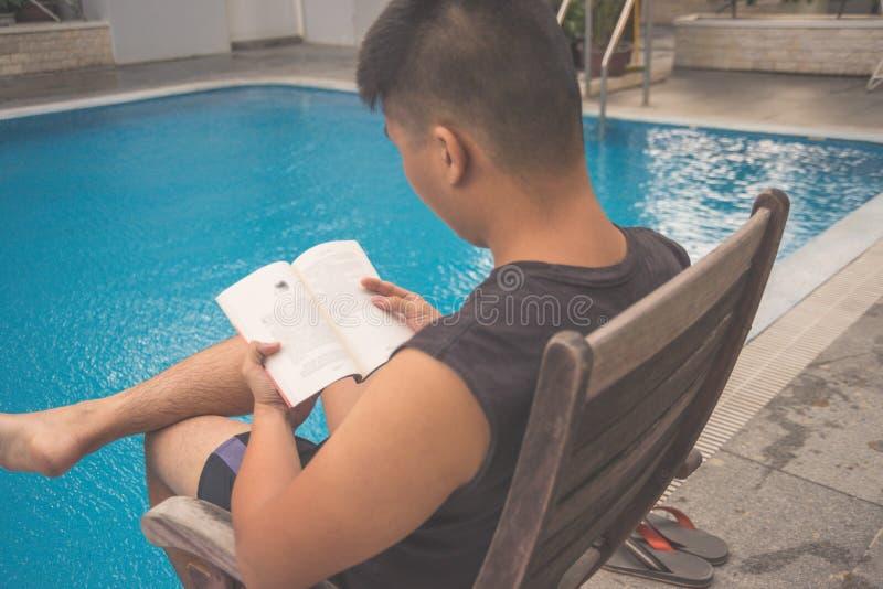 Libro de lectura del hombre en la piscina fotos de archivo