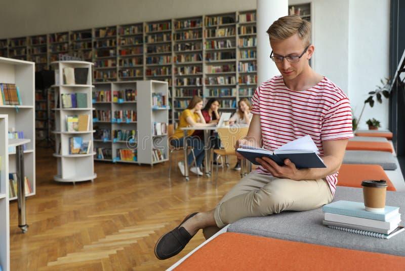 Libro de lectura del hombre joven en biblioteca foto de archivo libre de regalías