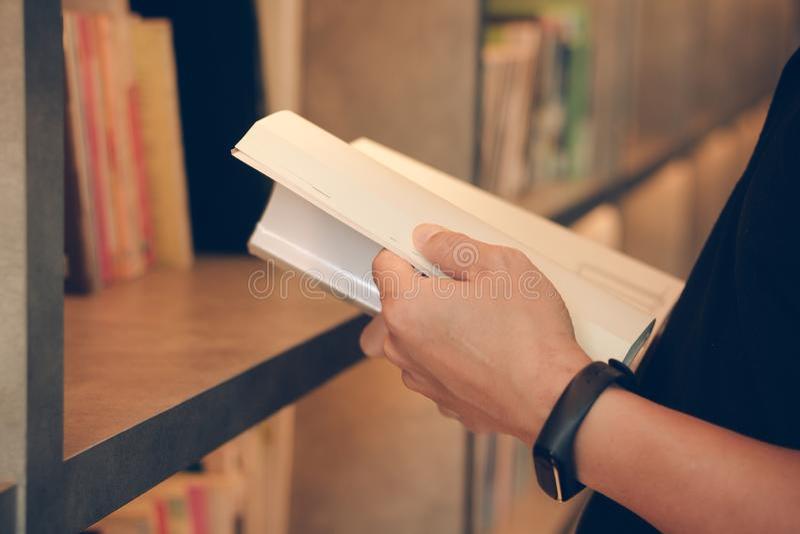 Libro de lectura del hombre joven en la biblioteca, cierre para arriba Estudiante en el estudio de universidad del libro, conocim imagen de archivo libre de regalías