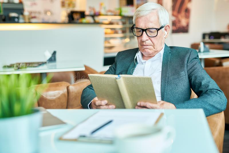 Libro de lectura del hombre mayor en café imagenes de archivo