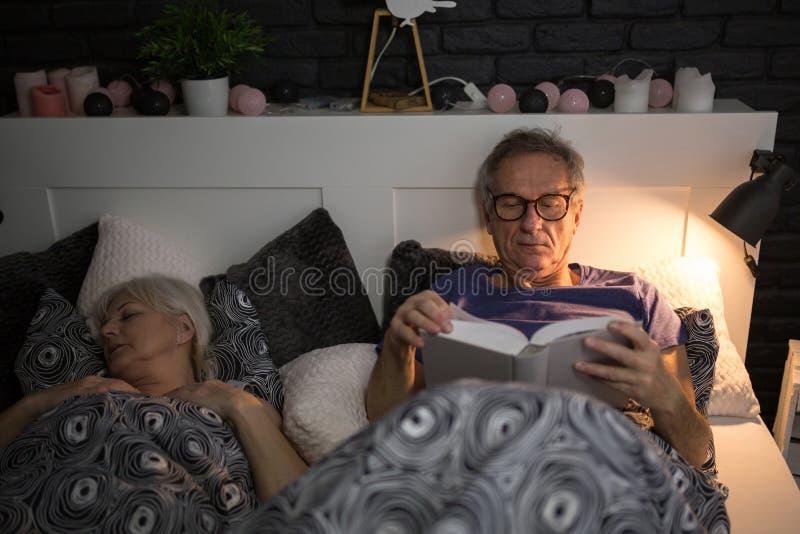 Libro de lectura del hombre mayor en cama antes del sueño foto de archivo libre de regalías