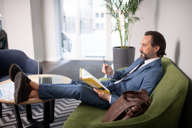 Libro de lectura del hombre de negocios mientras que se sienta cerca de la tabla con el ordenador portátil imagen de archivo