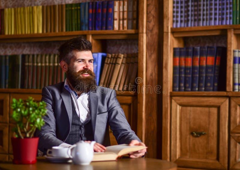 Libro de lectura del hombre y café de consumición imágenes de archivo libres de regalías