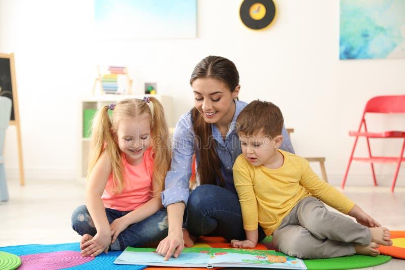 Libro de lectura del maestro de jardín de infancia a los niños Aprendizaje y el jugar fotografía de archivo