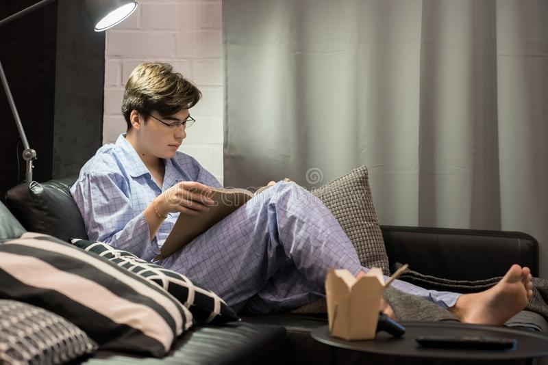 Libro de lectura del muchacho en pijamas imagen de archivo libre de regalías