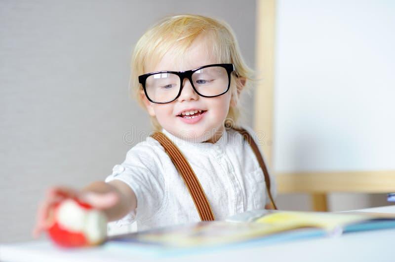 Libro de lectura del muchacho y manzana felices de la consumición en el lugar de trabajo imagenes de archivo