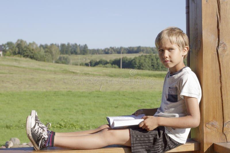 Libro de lectura del niño pequeño en la terraza del verano Ropa casual Fondo de la naturaleza Gente, educación, concepto del cono fotos de archivo libres de regalías