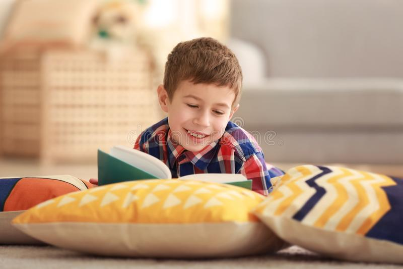 Libro de lectura del niño pequeño en piso con las almohadas fotos de archivo libres de regalías