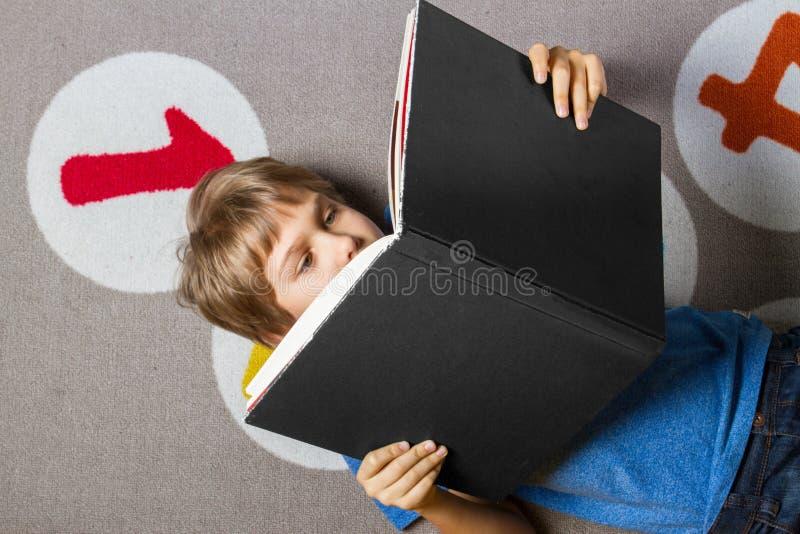 Libro de lectura del niño pequeño en un piso en casa imagen de archivo