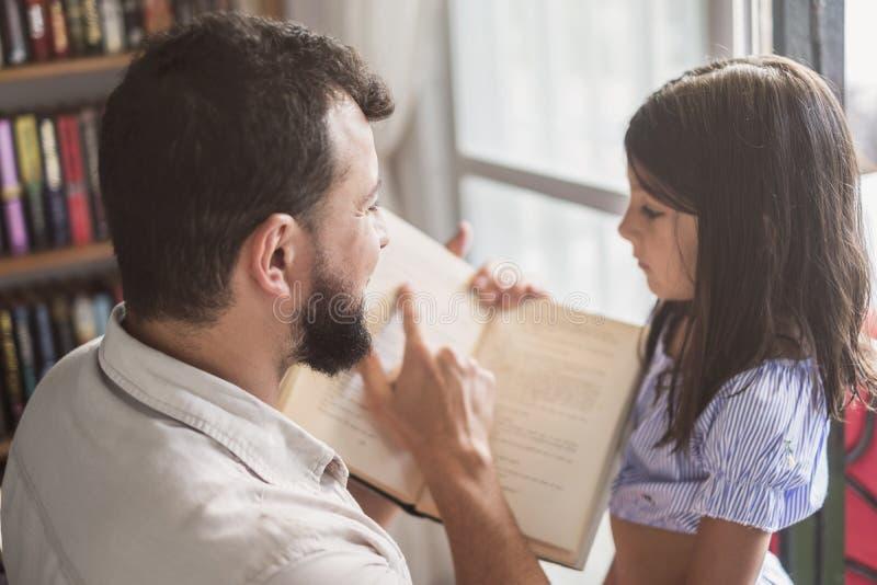 Libro de lectura del padre y de la hija cerca a la ventana fotografía de archivo