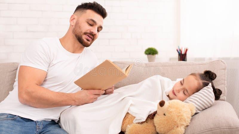 Libro de lectura del papá para su hija adorable durmiente foto de archivo libre de regalías