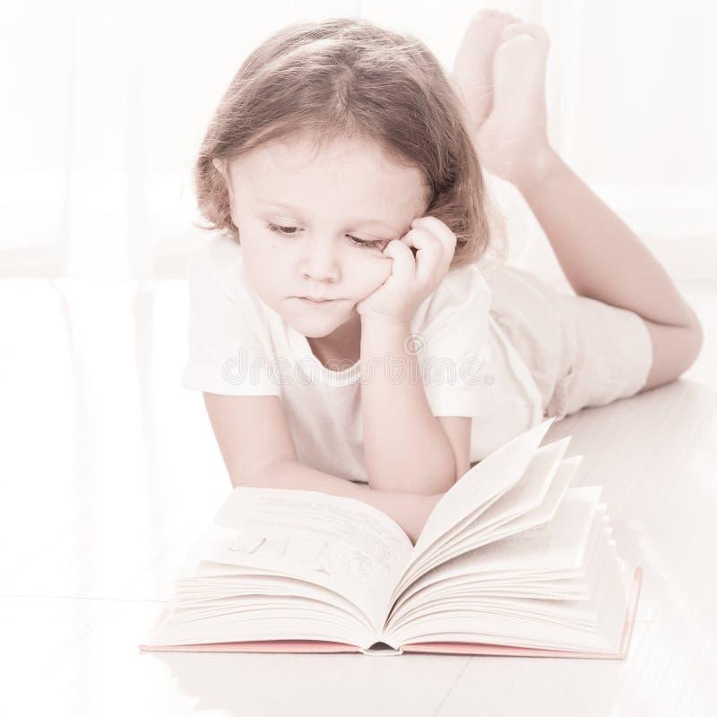 Libro de lectura del pequeño niño que se acuesta fotos de archivo libres de regalías