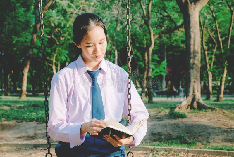 Libro de lectura del uniforme escolar del adolescente que lleva precioso mientras que se sienta en un oscilación en el parque imagen de archivo libre de regalías