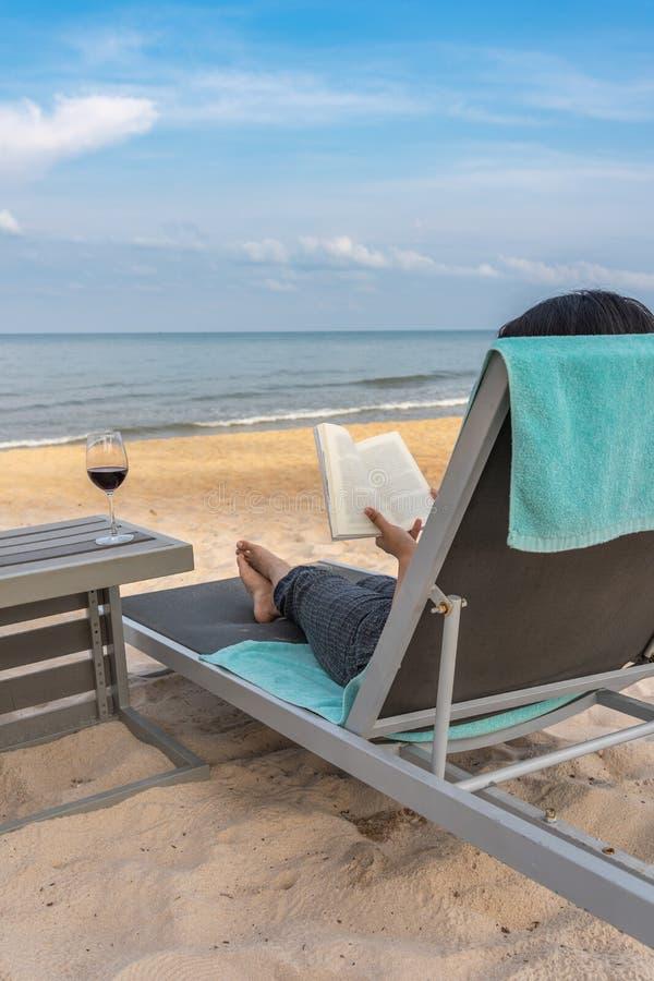 Libro de lectura del viajero con la copa de vino en la playa hermosa imagen de archivo