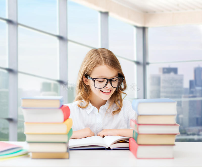Libro de lectura feliz de la muchacha del estudiante en la escuela foto de archivo
