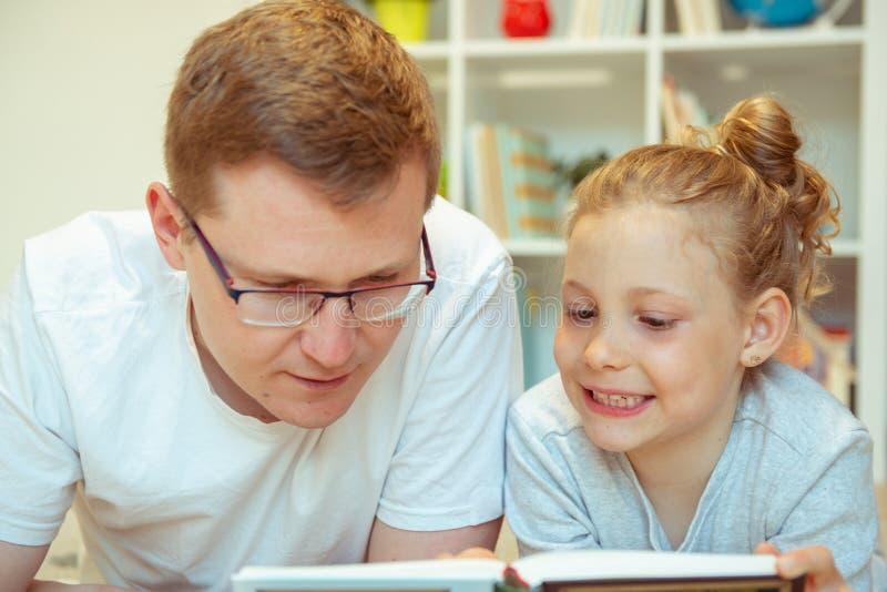 Libro de lectura feliz joven del padre con la hija linda en casa imagen de archivo libre de regalías