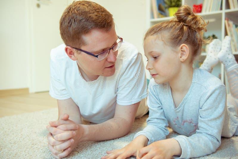 Libro de lectura feliz joven del padre con la hija linda en casa foto de archivo