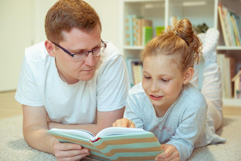 Libro de lectura feliz joven del padre con la hija linda en casa fotografía de archivo
