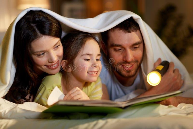 Libro de lectura feliz de la familia en cama en la noche en casa fotos de archivo libres de regalías