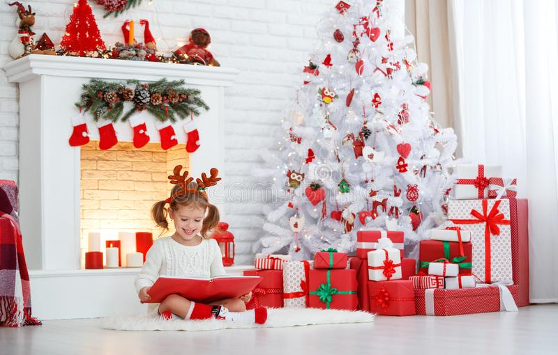 Libro de lectura feliz de la muchacha del niño por mañana en el árbol de navidad imagen de archivo