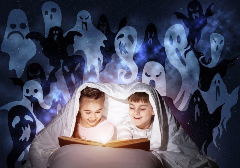 Libro de lectura feliz de los ni?os en cama fotografía de archivo libre de regalías