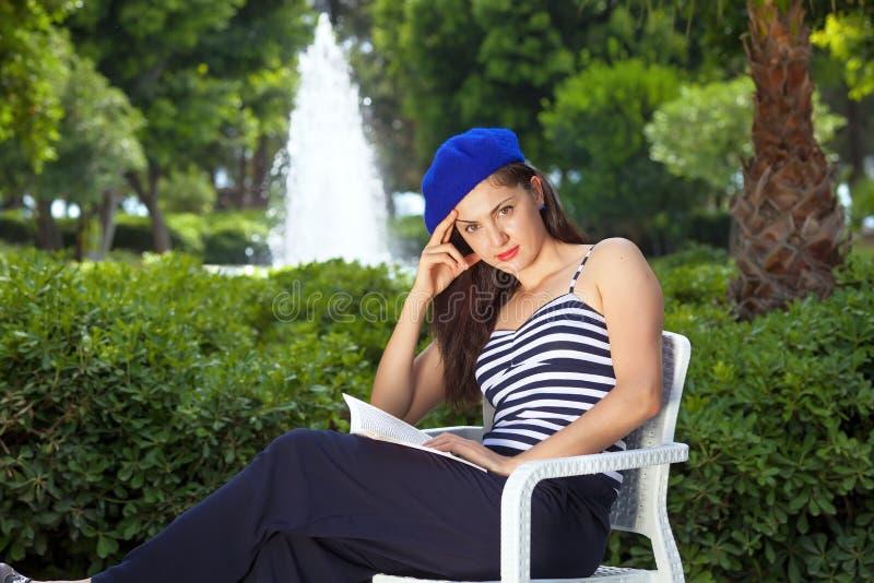 Libro de lectura femenino hermoso joven en parque. imagenes de archivo