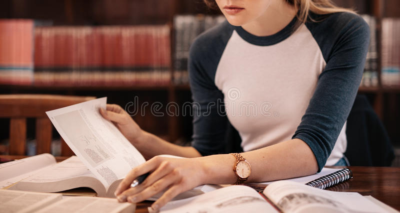 Libro de lectura femenino joven en la biblioteca fotos de archivo