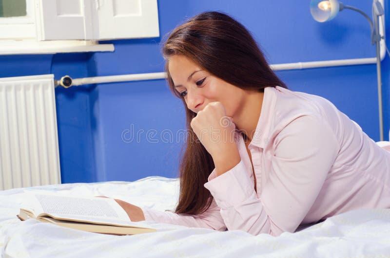 Libro de lectura hermoso de la muchacha en cama imagen de archivo