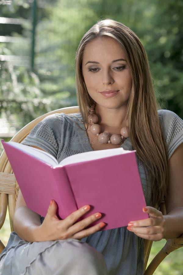 Libro de lectura hermoso de la mujer joven en parque fotografía de archivo libre de regalías