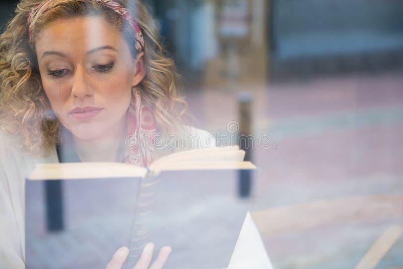 Libro de lectura hermoso de la mujer visto a través de ventana del café imágenes de archivo libres de regalías