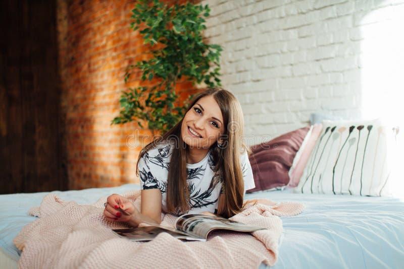 Libro de lectura hermoso de la mujer joven en cama fotografía de archivo libre de regalías
