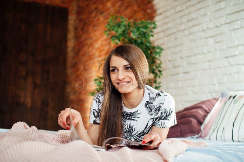 Libro de lectura hermoso de la mujer joven en cama foto de archivo