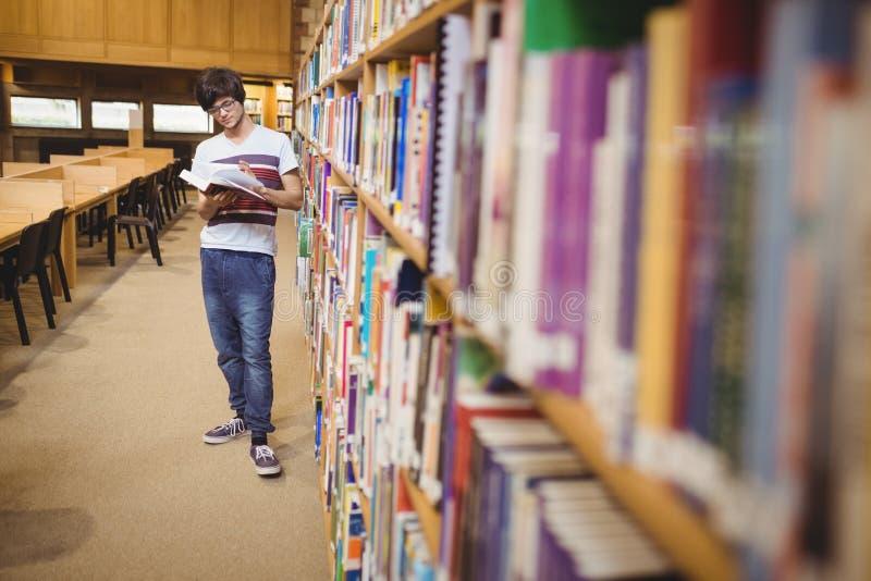 Libro de lectura joven del estudiante mientras que coloca el estante cercano foto de archivo