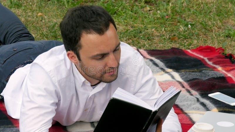 Libro de lectura joven hermoso del hombre de negocios que miente en el parque foto de archivo